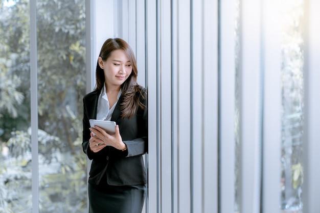 Mulher de negócio nova bonita asiática na saia do terno usando a tabuleta para trabalhar sobre vendas e plano de marketing