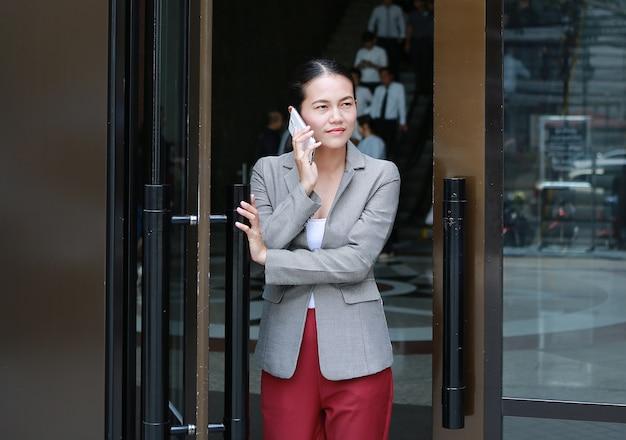 Mulher de negócio nova bonita que usa o telefone com porta aberta e andando fora.