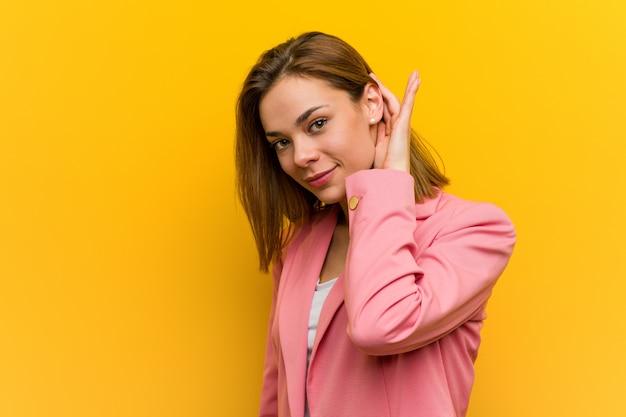 Mulher de negócio nova da forma que tenta escutar uma bisbolhetice.