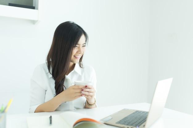 Mulher de negócio nova feliz que guarda o copo de café e que olha seu portátil. conceito de trabalho.