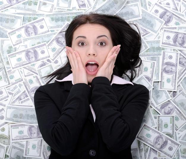 Mulher de negócio nova que descansa em cima do dinheiro.
