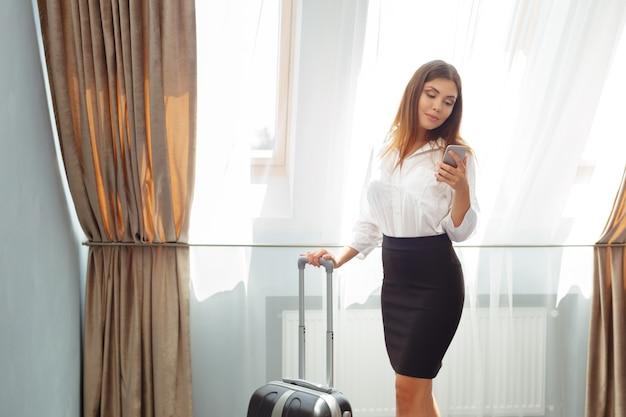 Mulher de negócio nova que fala com o telefone no hotel.
