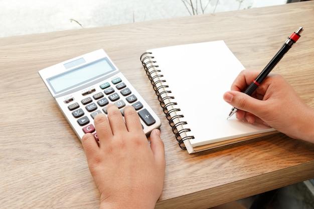 Mulher de negócio que empurra a calculadora com caderno e pena na mesa - conceito de trabalho.