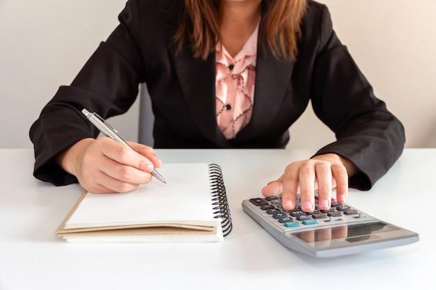 Mulher de negócio que empurra a calculadora na mesa - conceito de trabalho.