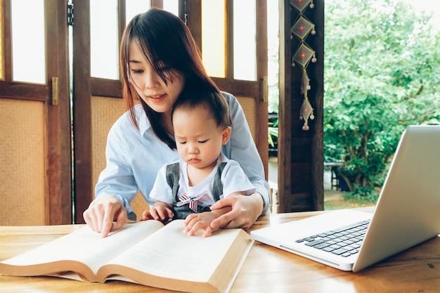 Mulher de negócio que ensina seu filho com portátil, tabuleta, e livro, educação escolar home.
