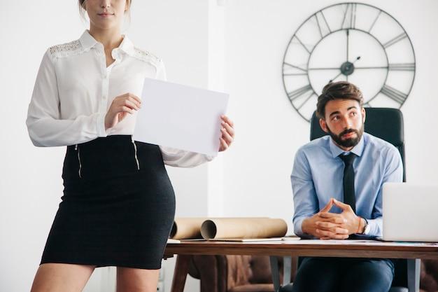 Mulher de negócio que mostra o papel no escritório