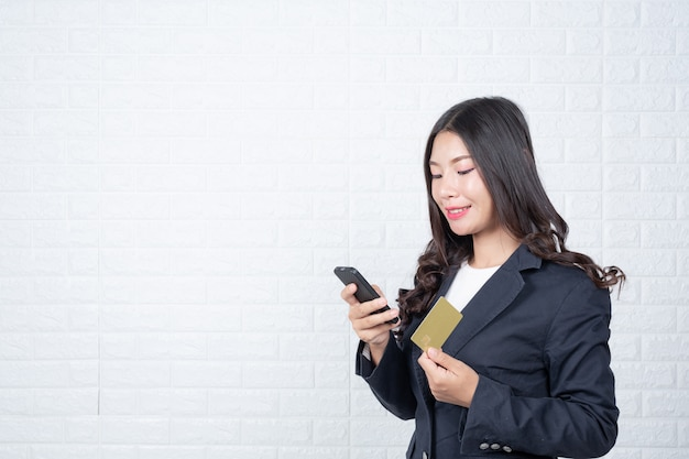 Mulher de negócio que prende um cartão separado do dinheiro, parede de tijolo branca gestos feitos com língua de sinais.