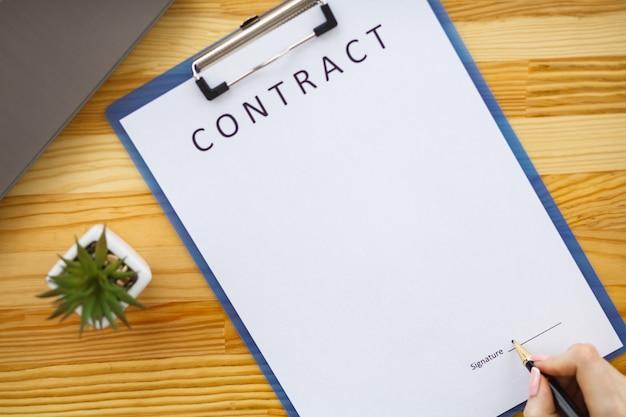 Mulher de negócio que senta-se na mesa de escritório que assina um contrato com foco raso na assinatura.