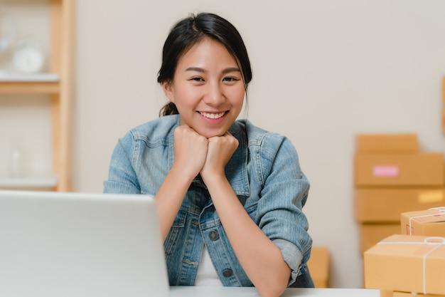 Mulher de negócio que sente feliz sorrindo e olhando à câmera ao trabalhar em seu escritório em casa.
