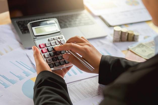 Mulher de negócio que usa a calculadora para trabalhar no escritório. conceito de finanças e contabilidade