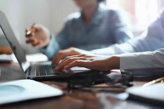 Mulher de negócio que usa a mão do portátil que datilografa no teclado para encontrar a equipe no escritório.