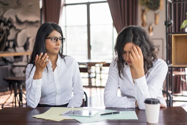 Mulher de negócio séria que acusa o colega de fazer o erro.