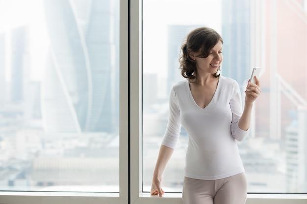 Mulher de negócio usando o telefone inteligente dentro