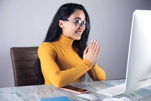 Mulher de negócios acenando olá no computador