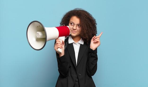 Mulher de negócios adolescente bonita e afro com um megafone