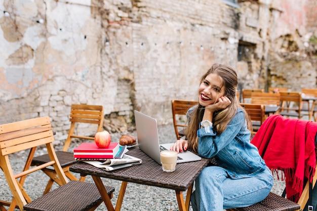 Mulher de negócios adorável com longos cabelos loiros, usando o computador laptop branco na pausa para o almoço no café ao ar livre no fundo da parede de tijolos. linda garota de jeans, sentada à mesa de madeira.