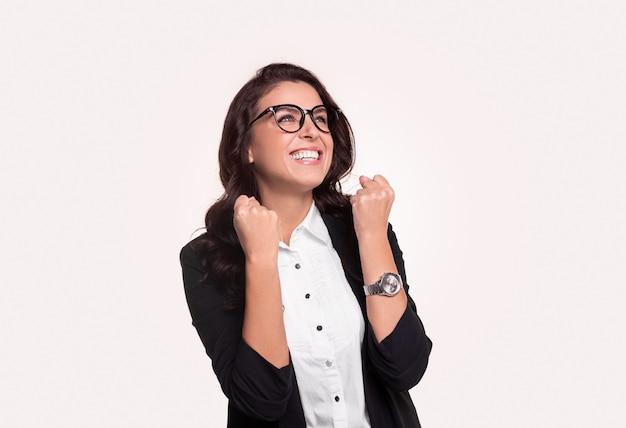 Mulher de negócios adulta animada com roupas formais e óculos cerrando os punhos enquanto celebra a conquista