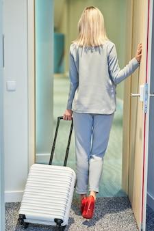 Mulher de negócios adulta saindo do quarto do hotel com uma mala