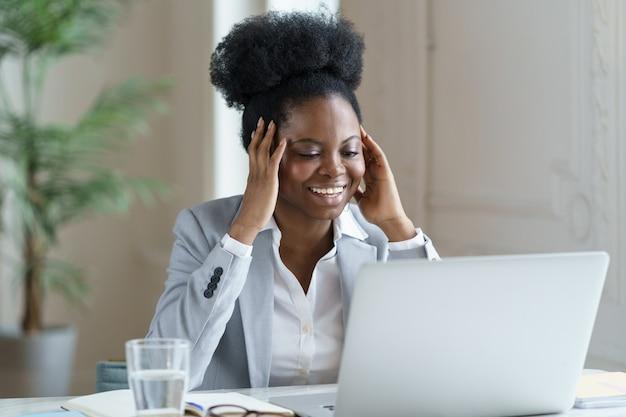 Mulher de negócios africana animada lendo e-mail de notícias positivas com oferta de emprego no laptop com sorriso feliz