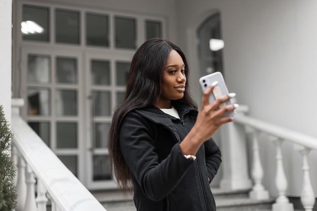 Mulher de negócios africana bonita elegante com smartphone fazendo videochamada na cidade. garota tirando uma selfie