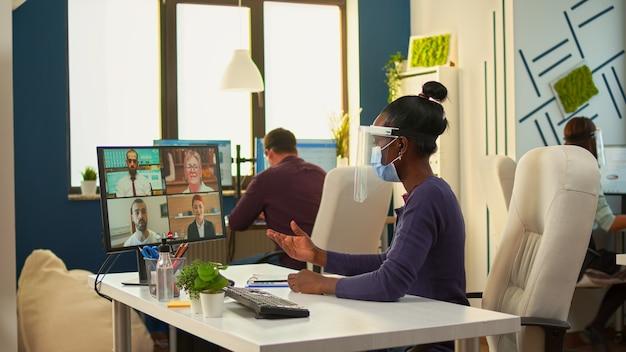 Mulher de negócios africana com máscara facial no escritório, falando em videochamada com equipe remota durante a epidemia de coronavírus. ter conferência online, videoconferência com colegas que trabalham respeitando a distância social.