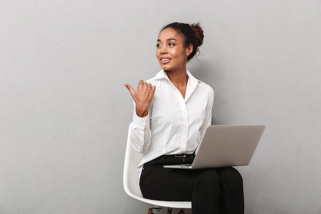 Mulher de negócios africana confiante vestindo terno sentado em uma cadeira, usando o computador laptop sobre cinza