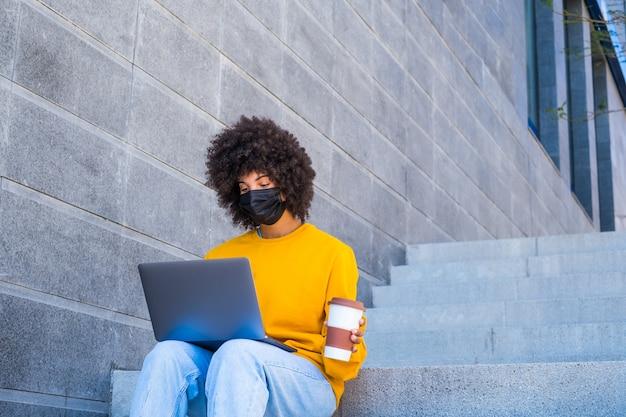 Mulher de negócios africana ou americana que trabalha sozinha na rua senta na escada da cidade usando seu laptop ou computador usando máscara