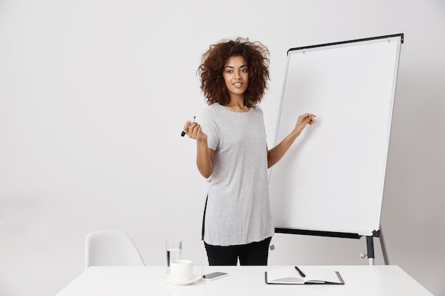 Mulher de negócios africana que sorri estando perto do quadro branco do marcador no escritório.