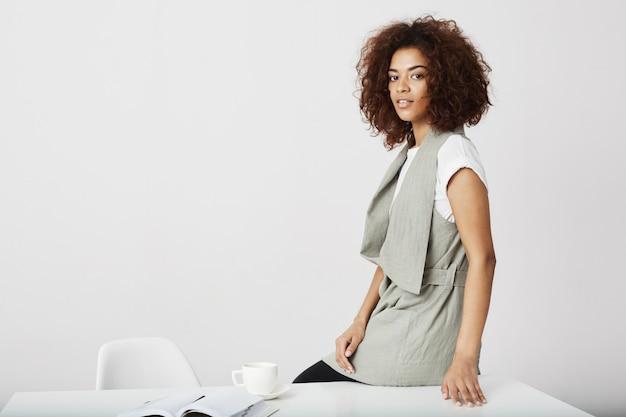Mulher de negócios africana que sorri sentado na mesa no local de trabalho sobre parede branca.
