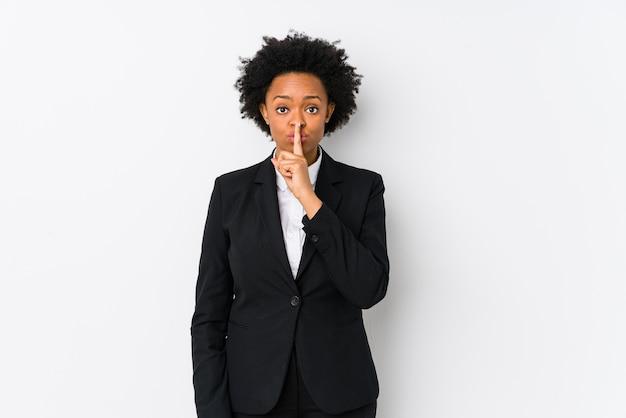 Mulher de negócios afro-americana de meia idade contra uma parede branca isolada, mantendo um segredo ou pedindo silêncio.