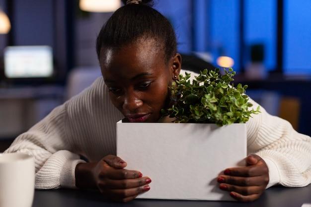 Mulher de negócios afro-americana despedida triste em pé com a cabeça sobre uma caixa de papelão