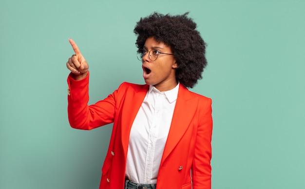 Mulher de negócios afro-americana espantada a apontar e a olhar para cima
