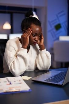 Mulher de negócios afro-americana exausta, massageando a testa com dor de cabeça