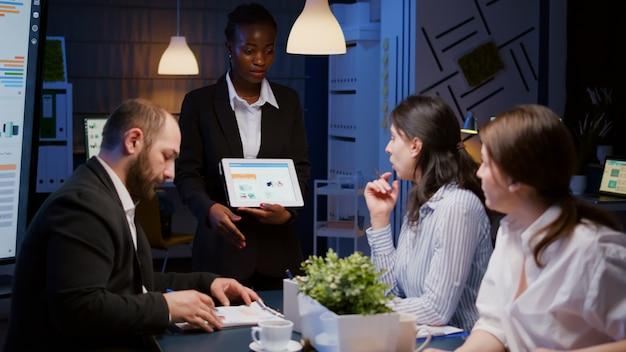 Mulher de negócios afro-americana focada em workaholic mostrando gráficos financeiros no tablet