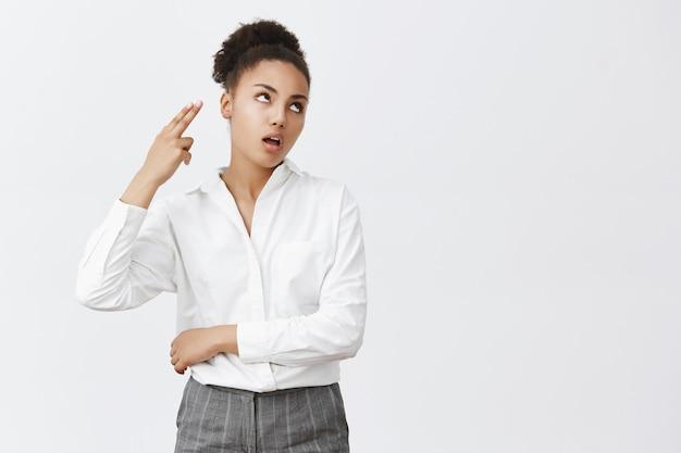 Mulher de negócios afro-americana irritada e incomodada revira os olhos e ofega, tornando o gesto de arma de mão entediado