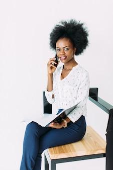 Mulher de negócios afro-americana jovem alegre falando no celular, sentado na cadeira, isolada no branco