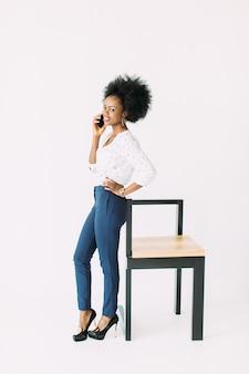 Mulher de negócios afro-americana jovem alegre falando no telefone celular, em pé perto da cadeira moderna, isolada no branco
