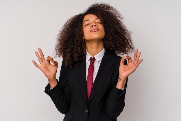 Mulher de negócios afro-americana jovem vestindo um terno isolado no branco relaxa após um árduo dia de trabalho, ela está realizando ioga.