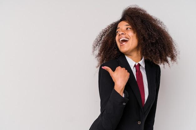 Mulher de negócios afro-americana jovem vestindo um terno isolado no fundo branco aponta com o dedo polegar afastado, rindo e despreocupada.