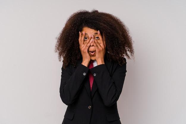 Mulher de negócios afro-americana jovem vestindo um terno isolado no fundo branco piscar por entre os dedos assustados e nervosos.