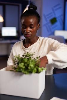 Mulher de negócios afro-americana realocada colocando objetos em uma caixa de papelão