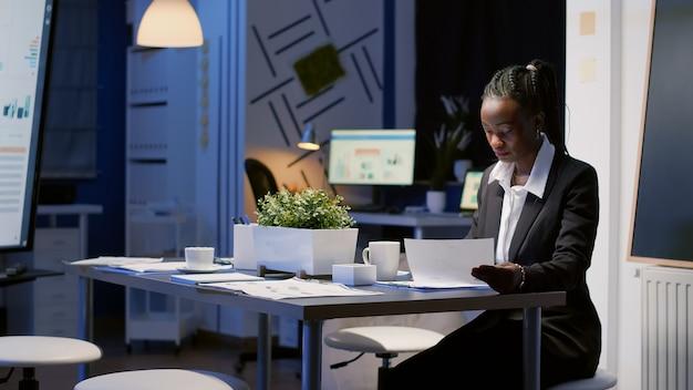 Mulher de negócios afro-americana sentada à mesa de conferência a beber café