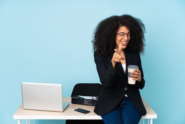 Mulher de negócios afro-americana trabalhando em seu local de trabalho, apontando para a frente e sorrindo