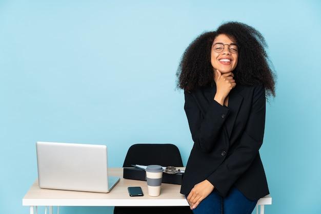 Mulher de negócios afro-americana trabalhando em seu local de trabalho com óculos e sorrindo