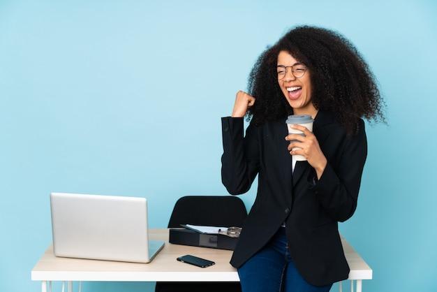 Mulher de negócios afro-americana trabalhando em seu local de trabalho e comemorando uma vitória