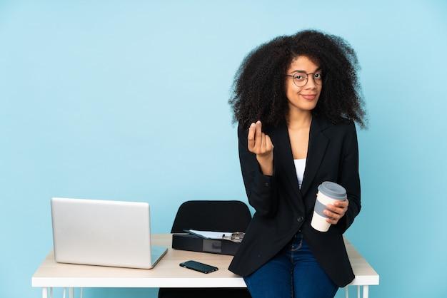 Mulher de negócios afro-americana trabalhando em seu local de trabalho fazendo gesto de dinheiro
