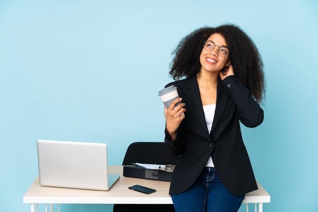 Mulher de negócios afro-americana trabalhando em seu local de trabalho, pensando em uma ideia