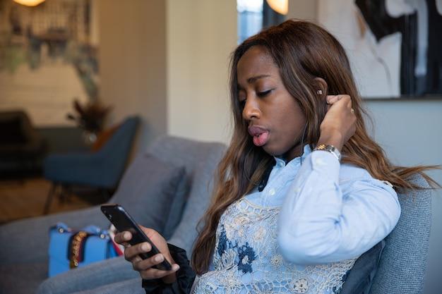 Mulher de negócios afro-americana usa seu smartphone e fones de ouvido para ouvir o áudio. ela está no escritório, sentada em uma poltrona