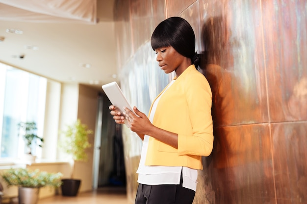 Mulher de negócios afro-americana usando computador tablet no escritório