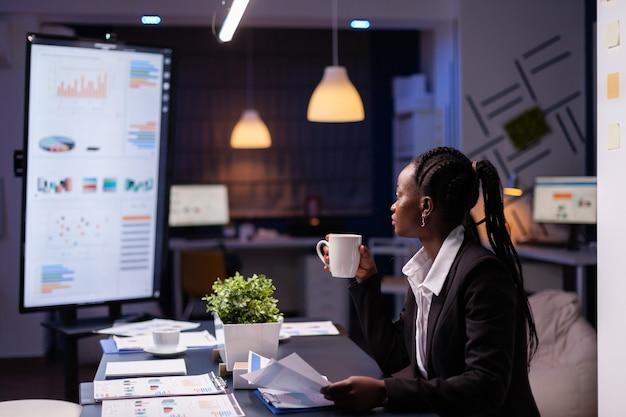 Mulher de negócios afro-americana viciada em trabalho analisando estatísticas de marketing na papelada